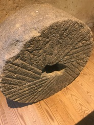Mill Stone: Early mills used mill stones to grind up grains into meal and flour. Note the pattern of grooves (furrows) cut into the stone. When another, identical stone is placed face down on top of this one the furrows cross each other, creating a shearing action as one stone turns.