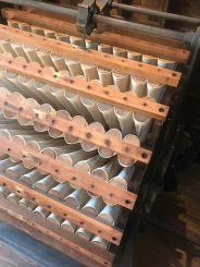 Tubular Dust Collector: This machine has 312cloth tubes arranged in rows around a rotating cylinder. The tubes are open to the center and dust-laden air entering the cylinder passes into the tubes allowing the debris to be captures there. Every time row of tubes reaches the top of the rotation, a hammer strikes the wooden bar joining the ends of that row together--causing the contents to drop into a trough. Anger moves the material to a spout to be carried downstairs and discarded.